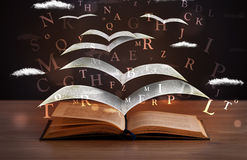 Pages and glowing letters flying out of a book Stock Images