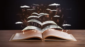Pages and glowing letters flying out of a book Stock Photos