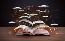 Pages and glowing letters flying out of a book Stock Photo