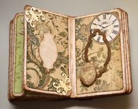 Pages of old-looking handmade photo album with clock, cameo and frame Stock Image
