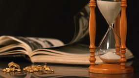 Pages turning in the wind beside hourglass and gold nuggets. In slow motion stock video footage