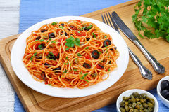 Paghetti with tomato sauce, capers and olives. Pasta spaghetti with tomato sauce, capers and olives on plate on  wooden cutting board with fork and knife Royalty Free Stock Photography