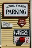 Paghi il segno di parcheggio ed il contenitore di soldi rosso sulla parete Fotografia Stock