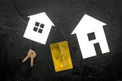 Paghi l'ipoteca Alloggi la siluetta vicino alle chiavi dell'appartamento e la carta assegni sulla vista superiore del fondo nero Fotografia Stock