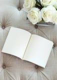 Pagina in bianco aperta del libro sul sofà con il fiore della rosa di bianco Fotografia Stock