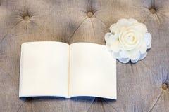 Pagina in bianco con la rosa di bianco sul sofà Immagine Stock Libera da Diritti