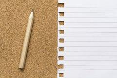 Pagina in bianco del blocco note con la matita su una superficie del sughero Fotografie Stock