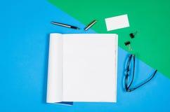 Pagina in bianco o rivista del modello sulla vista superiore del fondo variopinto Immagine Stock