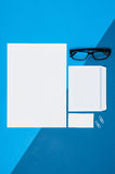 Pagina in bianco o rivista del modello sulla vista superiore del fondo variopinto Fotografia Stock