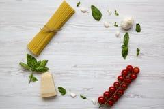 Pagina con gli ingredienti per la cottura della pasta su una tavola di legno bianca Disposizione piana Da sopra Copi lo spazio Fotografie Stock