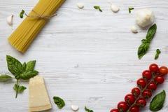 Pagina con gli ingredienti per la cottura della pasta su una tavola di legno bianca Disposizione piana Da sopra Copi lo spazio Fotografie Stock Libere da Diritti