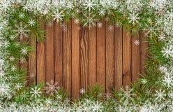 Pagina con i ramoscelli dell'albero di Natale ed i fiocchi di neve su legno Fotografia Stock
