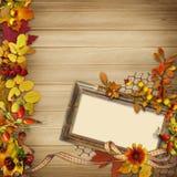 Pagina con le foglie e le bacche di autunno su un fondo di legno Fotografia Stock Libera da Diritti