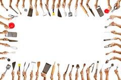 Pagina con le mani che tengono molti strumenti della cucina immagine stock