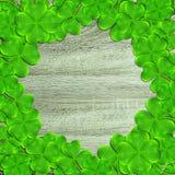 Pagina dalle foglie o dalle acetoselle verdi del trifoglio su fondo di legno Fotografia Stock