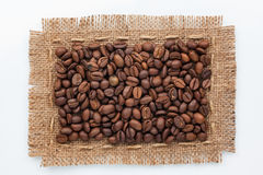 Pagina dei chicchi di caffè e della tela da imballaggio che si trovano su un fondo bianco Fotografia Stock Libera da Diritti