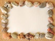 Pagina dei ciottoli marini su un Libro Bianco sulla sabbia Immagini Stock