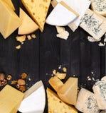 Pagina dei tipi differenti di formaggi sulla tavola nera Vista superiore, spazio della copia Cheddar, parmigiano, emmental, forma Immagini Stock