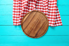 Pagina del tagliere rotondo e della tovaglia rossa del plaid Fondo di legno blu nel caffè Vista superiore Immagini Stock