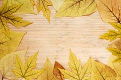 Pagina delle foglie di autunno gialle su un fondo di legno Cartolina d'auguri di autunno con le foglie Spazio vuoto per testo immagini stock