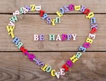 Pagina delle lettere di legno colorate nella forma di cuore e testo & x22; Sia happy& x22; Immagini Stock