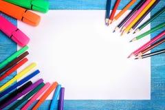 Pagina delle matite colorate intorno ad uno strato bianco su un backgr di legno Immagini Stock