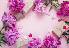 Pagina delle peonie, dei contenitori di regalo e dei cuori decorativi su un BAC rosa Immagini Stock Libere da Diritti
