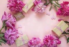 Pagina delle peonie, dei contenitori di regalo e dei cuori decorativi su un BAC rosa Fotografia Stock Libera da Diritti