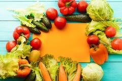 Pagina delle verdure con la carta di ricetta su fondo di legno blu Vista superiore immagini stock libere da diritti