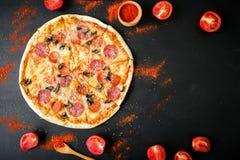 Pagina di pizza italiana saporita con gli ingredienti e le spezie su fondo scuro Disposizione piana, vista superiore fotografia stock