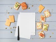 Pagina e cracker del libro di ricetta con formaggio cremoso e varie guarnizioni Aperitivi sulla tavola grigia Vista superiore, di immagini stock libere da diritti