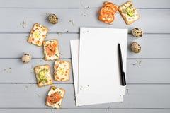 Pagina e cracker del libro di ricetta con formaggio cremoso e varie guarnizioni Aperitivi sulla tavola grigia Vista superiore, di immagine stock libera da diritti
