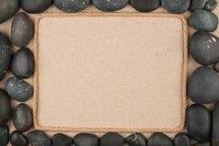 Pagina fatta della corda che si trova sulla sabbia fra le pietre nere fotografia stock