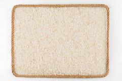 Pagina fatta della corda con i grani del riso che si trovano su un fondo bianco Fotografia Stock