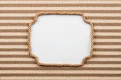 Pagina fatta della corda con un fondo bianco sulla sabbia Immagini Stock