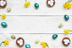 Pagina fatta delle uova di Pasqua, dei fiori della molla e delle piume su fondo di legno bianco Compisition di Pasqua Fotografia Stock Libera da Diritti