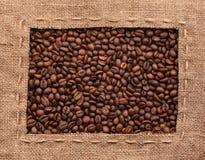 Pagina fatta di tela da imballaggio con i chicchi di caffè Fotografie Stock