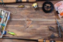 Pagina le attrezzature di pesca e le esche di pesca in scatole sul fondo del bordo di legno fotografia stock