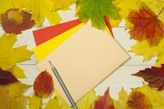 Pagina le foglie di autunno con la busta beige su fondo di legno Modello variopinto per progettazione fotografia stock