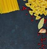 Pagina per alimento Ingredienti della pasta Pomodori ciliegia, pasta degli spaghetti, aglio e spezie su un fondo scuro di lercium immagine stock