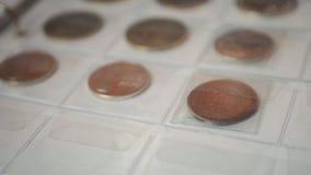 Pagina van geïsoleerde numismatiekalbum met verschillende muntstukken De inzameling van het muntstukalbum van verschillende lande stock video