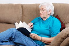Paginaciones de torneado de la mujer mayor de un libro imagenes de archivo