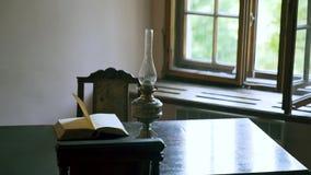 Pagine del libro che girano dal vento sulla tavola con la lampada a olio in vecchio gabinetto 4K archivi video