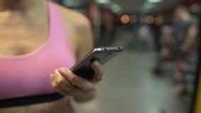 Pagine di scorrimento della donna sul suo telefono cellulare, avendo rottura dall'esercitazione in palestra stock footage