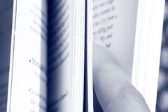 Paging a book. Hand paging a book - colored in blue Royalty Free Stock Photos