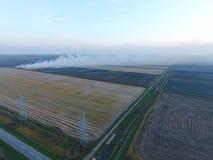 Paglia bruciante nei campi dopo avere effettuato il raccolto del grano Fotografia Stock Libera da Diritti