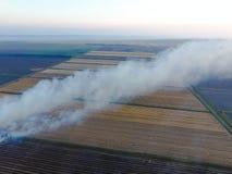 Paglia bruciante nei campi dopo avere effettuato il raccolto del grano Fotografie Stock