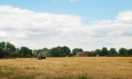 Paglia d'imballaggio del trattore rosso in un campo dell'azienda agricola Fotografia Stock