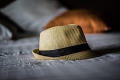 Paglia del cappello sul letto, natura morta Immagini Stock