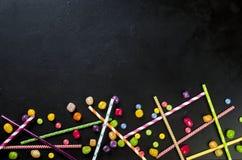 Paglia del cocktail e mini caramella su un fondo nero, vista superiore, Fotografie Stock Libere da Diritti